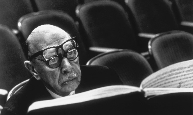 Igor Stravinsky wearing two pairs of glasses while reading musical score during a rehearsal